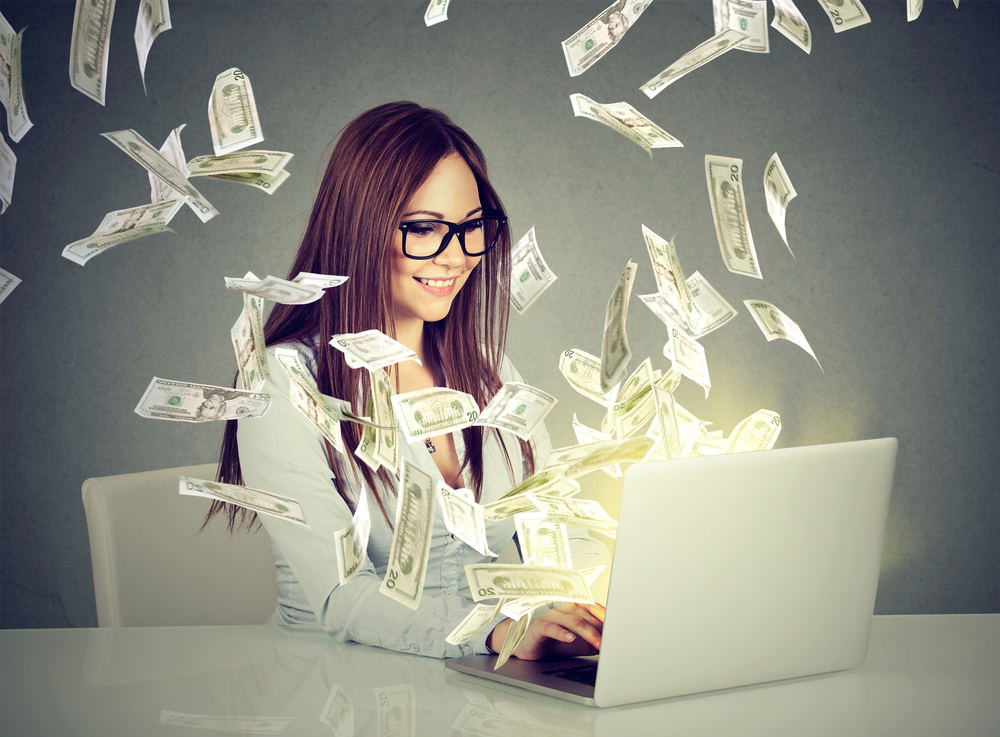 Person working on a laptop with money notes flying around