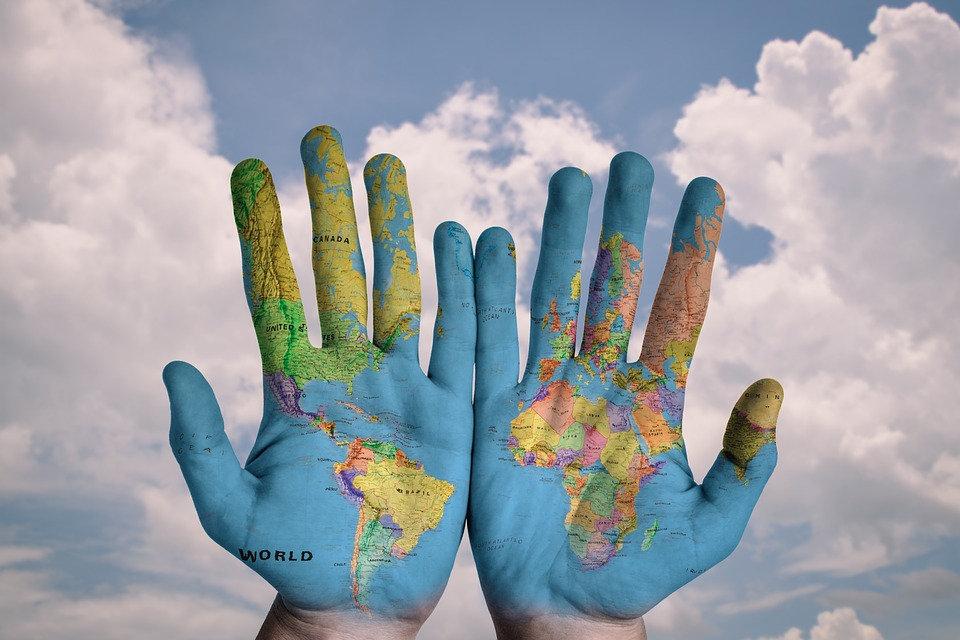 Hands showing a map of the world