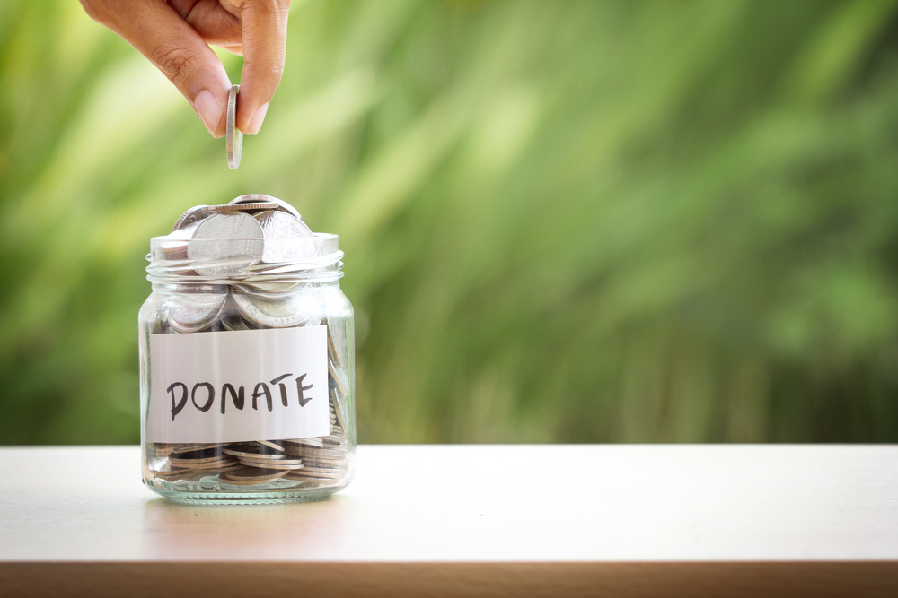 Person adding coins to donate jar - fundraising