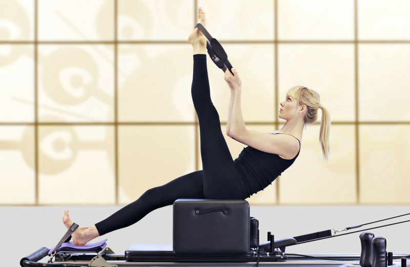 Ten Health and Fitness - woman doing a Pilates reformer workout
